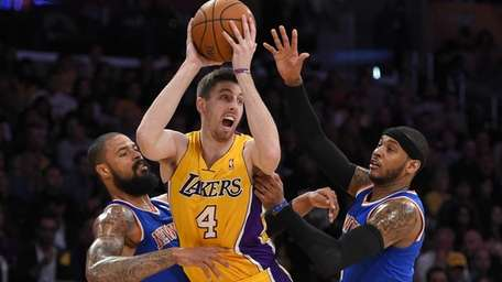 Los Angeles Lakers forward Ryan Kelly, center, tries