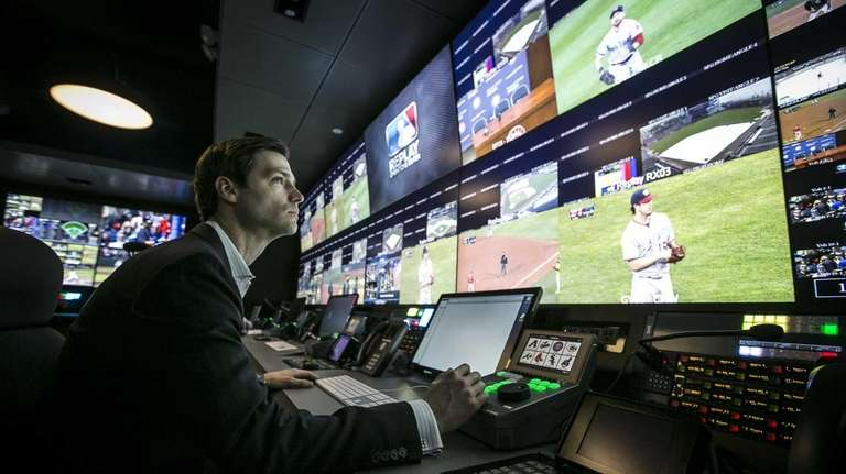 Workers demonstrate Major League Baseball's instant replay center,