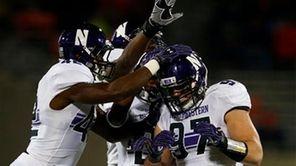 Teammates celebrate with Northwestern defensive lineman Tyler Scott,
