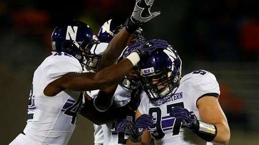 Teammates celebrate with Northwestern defensive lineman Tyler Scott,