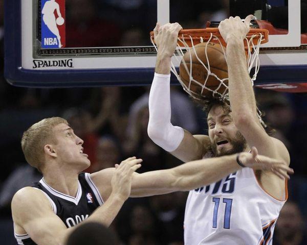 Charlotte Bobcats' Josh McRoberts, right, dunks as Nets'