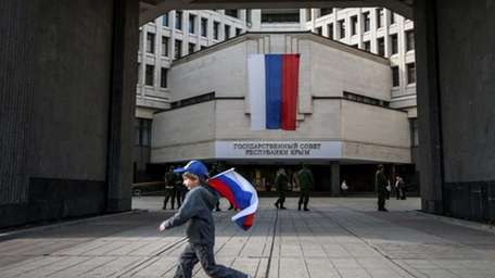 A boy runs with a Russian national flag