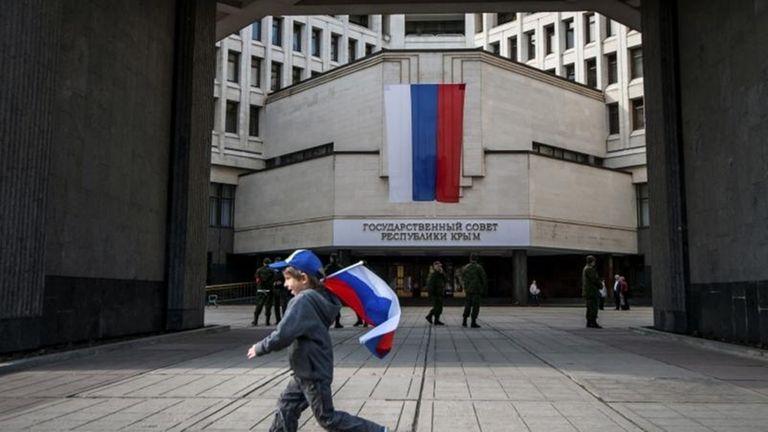 A boy runs with a Russian national flag