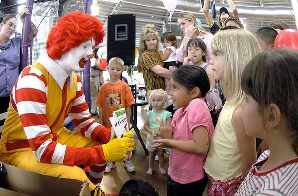 Ronald McDonald visits with children at a McDonald's