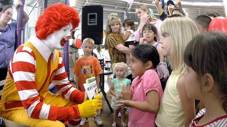 Ronald McDonald visits with children at a McDonald's