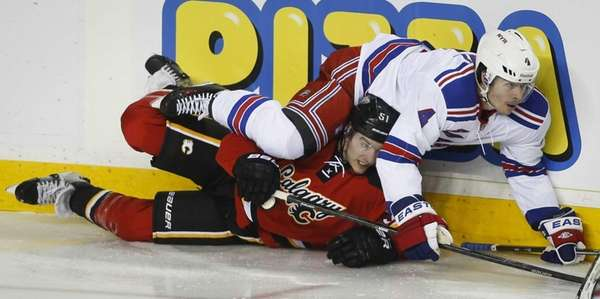 Rangers' Raphael Diaz, right, crashes over Calgary Flames'