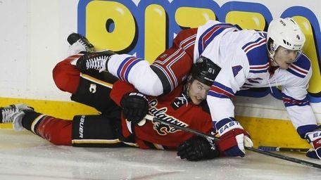 Rangers' Raphael Diaz, right, crashes over Calgary Flames'