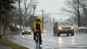 A man rides his bike through the rain