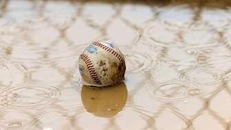 A baseball lays in the mud during a