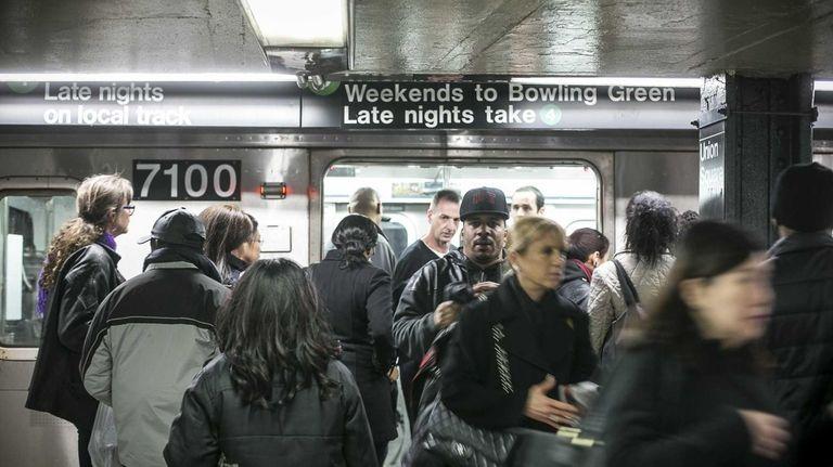 Riders walk through a crowded Union Square subway