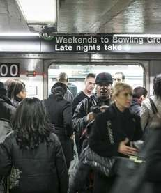 Riders walk through a crowded Union Square subway
