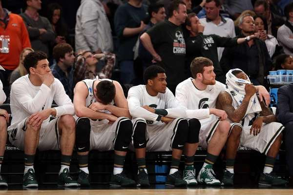 The Michigan State Spartans bench looks on late