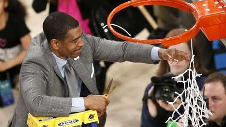 Connecticut head coach Kevin Ollie cuts the netting