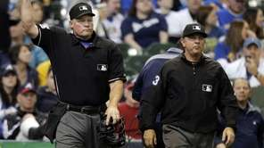 Umpire Ted Barrett, left, signals an out call