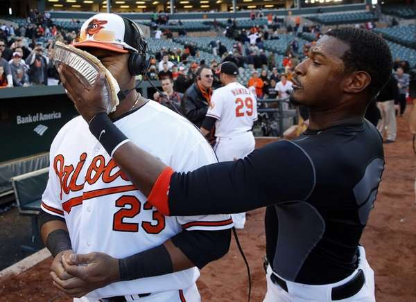 Baltimore Orioles outfielder Adam Jones, right, smears a