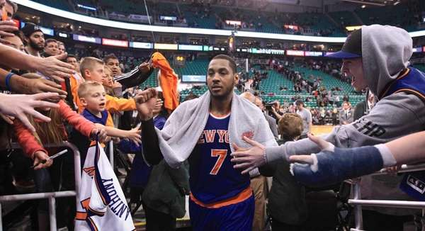 Fans reach for Carmelo Anthony (7) as he