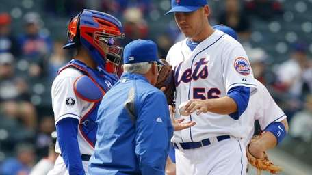 Scott Rice of the Mets hands the ball
