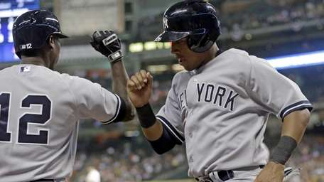 Yankees' Yangervis Solarte, right, knock arms with teammate