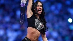 AJ Lee celebrates after defeating 13 over competitors