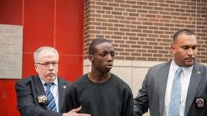 Marcell Dockery, 16, is walked by two police