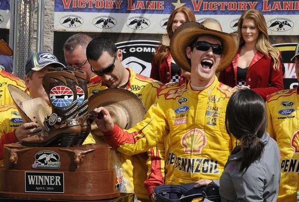 Joey Logano touches the winner's trophy in victory