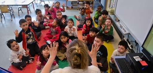 Kindergarten teacher Melissa Mazzalonga asks students questions inside