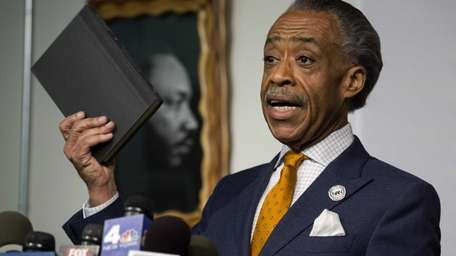 The Rev. Al Sharpton, while holding his autobiography,