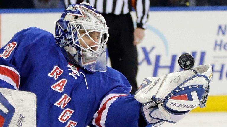 Rangers goalie Henrik Lundqvist catches a Carolina Hurricanes