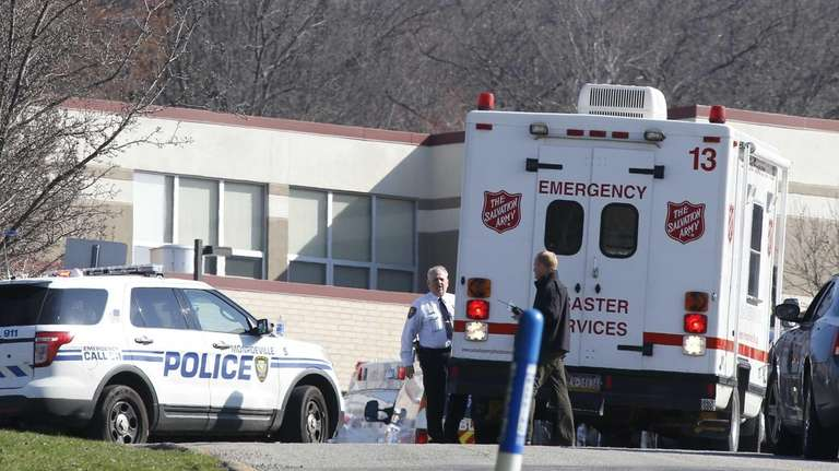 Emergency responders gather in the parking lot of