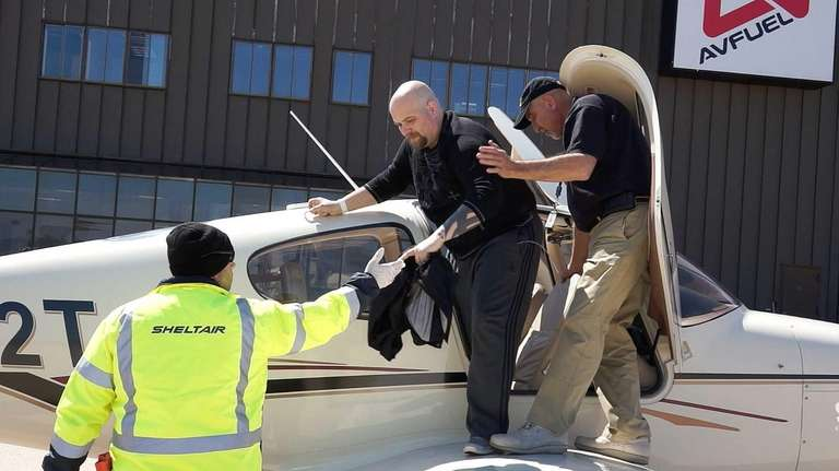 Christopher Kowalewski is helped from a plane by