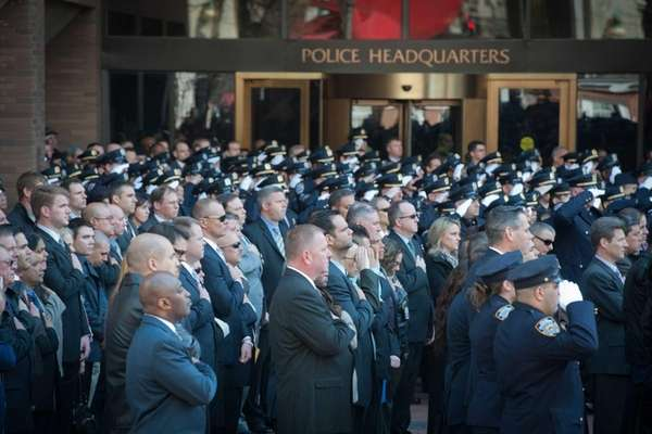 Police officers salute as Police Commissioner William J.