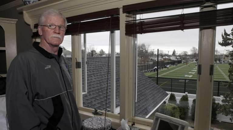 Greg Lane stands at the window of his