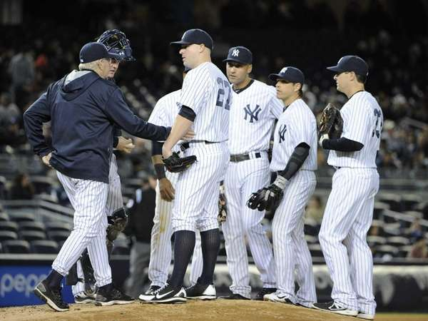 Yankees pitching coach Larry Rothschild speaks with pitcher