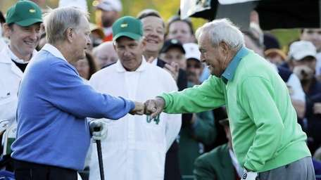 Jack Nicklaus, left, and Arnold Palmer touch fists