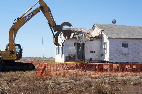 Workers begin demolishing a house in Mastic Beach