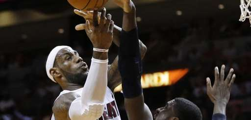 Miami Heat's LeBron James, left, shoots over Indiana