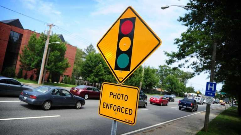Traffic moves past the sign for the red-light