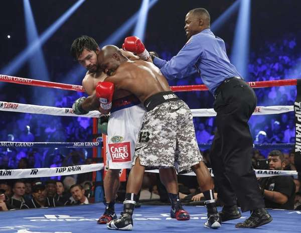 Timothy Bradley, center, hangs on to Manny Pacquiao,