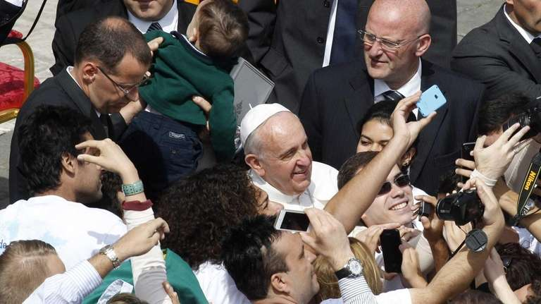 Faithful take pictures with Pope Francis at the