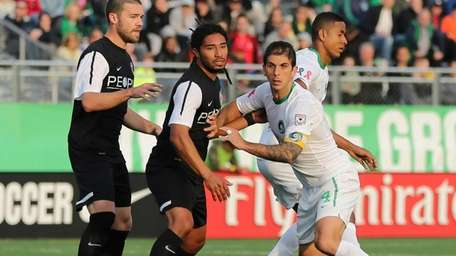 Cosmos captain Carlos Mendes #4 fights for position