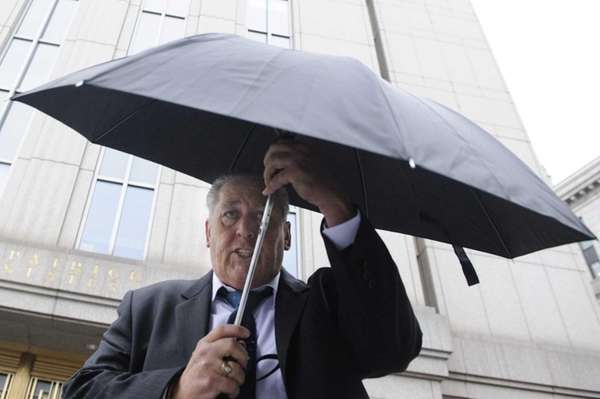 Daniel Denis tries to use an umbrella to