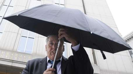 Daniel Denis tries to use an umbrella to
