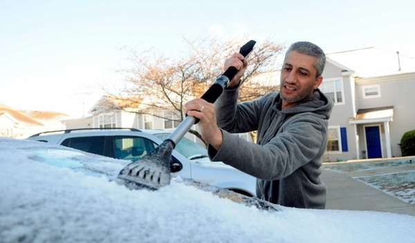 Ahmed Ghaddfi scraps ice off the windshield of