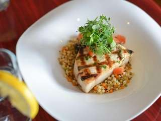 Expertly grilled swordfish with roasted tomato couscous, quinoa