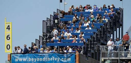 Fans watch from special seats through Wrigley Rooftops