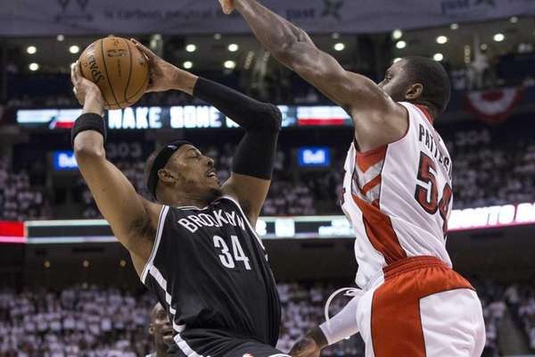 Nets' Paul Pierce, left, looks to pass beyond