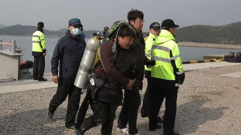 Divers arrive at the port on April 19,