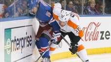 Mark Streit of the Philadelphia Flyers checks Derek