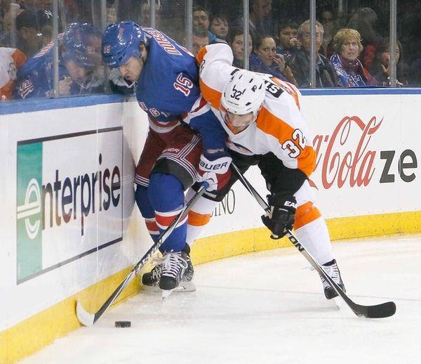 Mark Streit of the Philadelphia Flyers checks Derek