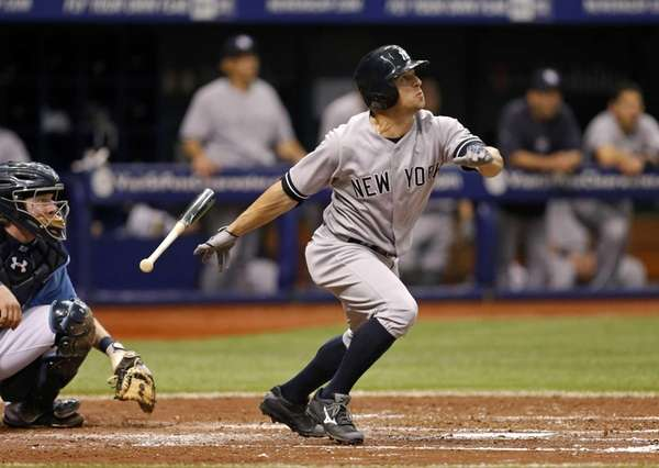 Yankees' Brett Gardner, right, follows through on a